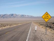 「低空飛行物体に注意」の道路標識