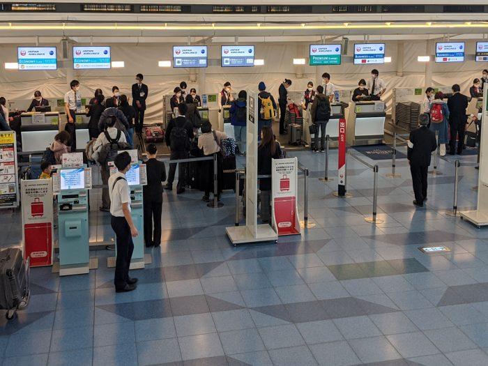 羽田空港・国際線ターミナルの日本航空のチェックインカウンター。スタッフ全員がマスクをしていることがわかる。