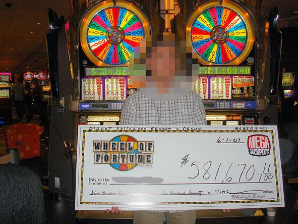約58万ドルの小切手の目録を手にするラッキーさん。
