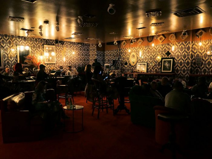 大小さまざまなテーブルやイスが並ぶ暗い照明の客席。